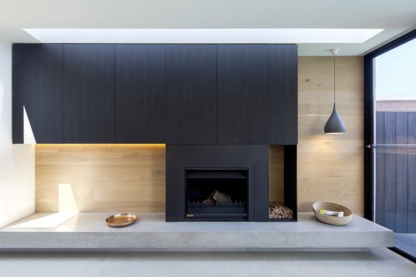 """The fireplace feature wall has a concrete hearth, oak paneling, and wall-mounted cabinetry with pre-finished door slabs from New Age Veneers in the """"Ravenswood"""" finish. A steel box integrated to the side of the fireplace stores wood, and glass walls make the most of the small site."""