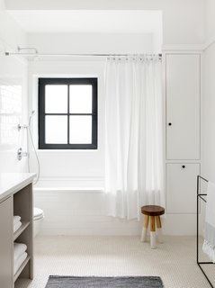 The white subway tile on the tub surround and cream penny rounds on the floor (both from Nemo Tile) create textural contrast in the same color palette. The stool is from Serena & Lily.