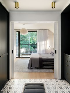 The view into the bedroom shows closet. Cabinetry has been integrated on both sides, and the walls have been painted with Benjamin Moore Flint.