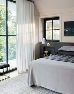 The headboard is also painted in Benjamin Moore Flint and sports a bedside niche, which is adorned with a walnut shelf and sconce from Rejuvenation. The delightful drapery on the windows is from The Shade Store.