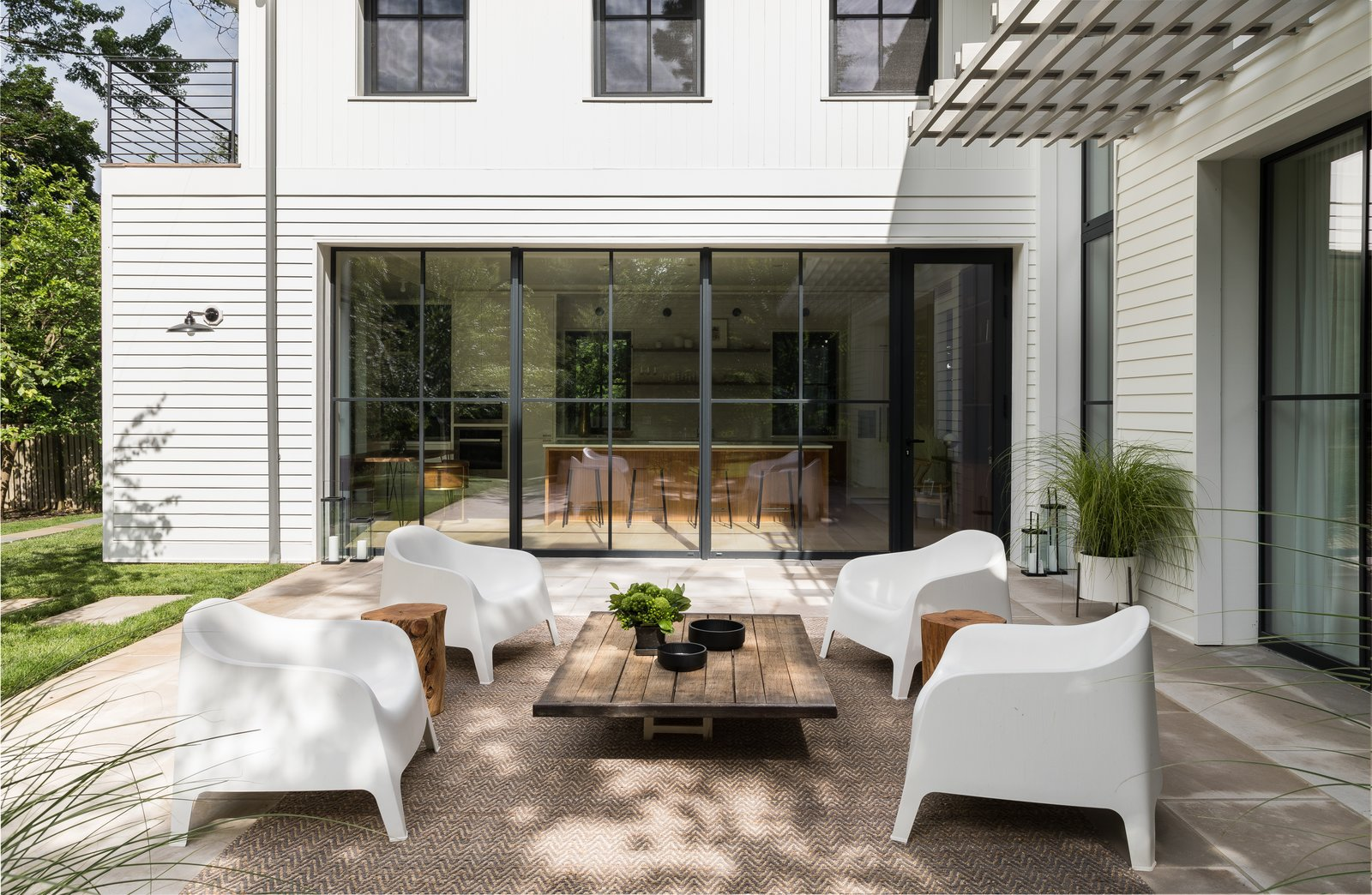 Outdoor, Large Patio, Porch, Deck, Back Yard, Stone Patio, Porch, Deck, Planters Patio, Porch, Deck, Hanging Lighting, Trees, and Grass A limestone terrace beckons off the main living areas. The white outdoor chairs are from IKEA.  Photo 13 of 16 in A New Jersey Neighborhood Gets a Gorgeous Passive House