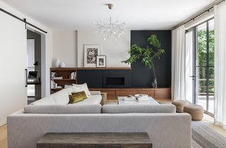 """Walnut storage, both open and closed, frames a black-painted wall with a fireplace at its center. The wall treatment can also hide a future television. """"A dark wall is a great way to keep a large screen from feeling like a big black hole on the wall,"""" notes the firm."""