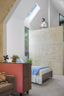 The bedroom area is tucked behind a vintage dresser with a new hot pink back, which makes an eye-catching space divider. A custom plywood panel wall provides discreet storage and hides the laundry machines.