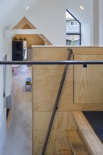 A custom steel railing on the ladder leads to the loft.