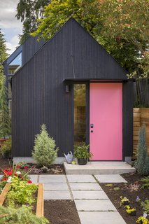 The garage door was replaced with a new entry to the building, featuring a custom steel canopy over the front door. The door is painted Benjamin Moore Flamingo's Dream to better contrast with the black-stained, tight-knot vertical cedar siding.