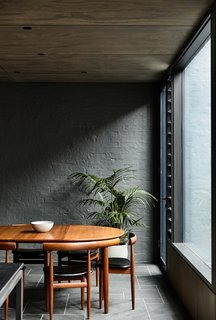In the dining room, a vintage dining set is offset by the painted brick wall of the original house. Lowered ceilings in the eating area provide an intimate setting within the larger space.