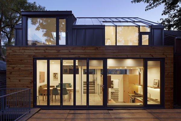 In order to maximize space, the architects utilized a split-level design that includes the living areas on the main level, two upstairs bedrooms, and a walk-out basement beneath the dining room. The wood siding was salvaged and restored from the previous building on-site, in order to bring warmth to the gray, seamed metal and reference the neighborhood's past.