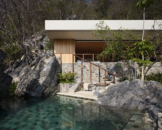 The sand-colored fascia of the roofline integrates the palapa into its environment, as does the stone wall facade, which blends in with the boulders.