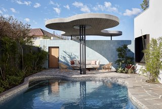 The architects brought the undulating lines outside with the pool's shape and overhead awning.