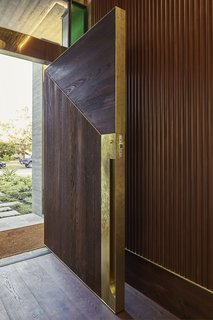 At the custom front door, textured wood is accented with un-lacquered brass to encourage patina with use.