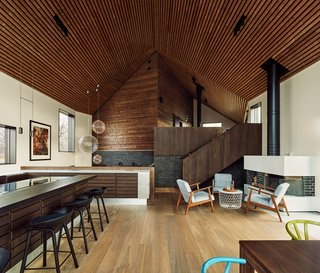 """""""They wanted a very practical house, with separate zones for kids and adults,"""" said Taugbøl. """"Because of the split levels, the experience of the space varies when you walk through it,"""" and ascend the staircase. """"The acoustics are also great due to the wood paneling in the ceiling."""" The Raimond pendent lights are from moooi, and the fireplace seating is IKEA."""