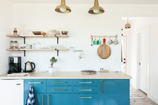 A small kitchenette allows guests to brew a cup of coffee or tea, or prepare a light meal. The brilliant blue, high-gloss cabinets are IKEA, similar to the KALLARP line, adorned with Schoolhouse Electric's Edgecliff Pulls. An oak wood countertop completes the picture.