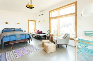Seen here, Tu Casa is decked out in stylish, second-hand finds, bright pink pillows from Collectivo, and lighting from Schoolhouse Electric, including the Isaac and Satellite Sconces.