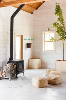 Shiplap pine walls, primed white, complement unfinished concrete floors and a wood stove by Jotul.