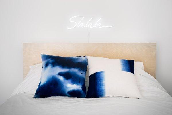 An IKEA bedframe with custom art above it.