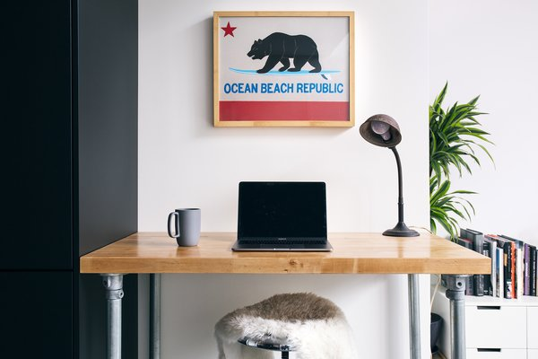 Kevin uses the desk as a work station, with room to spread over the centralized peninsula. Well-planned storage conceals office supplies when the work day is over.