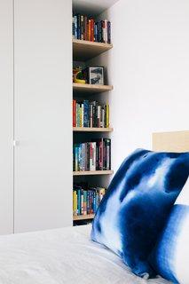 Sleek closets meet open inset shelves that echo the kitchen shelving.