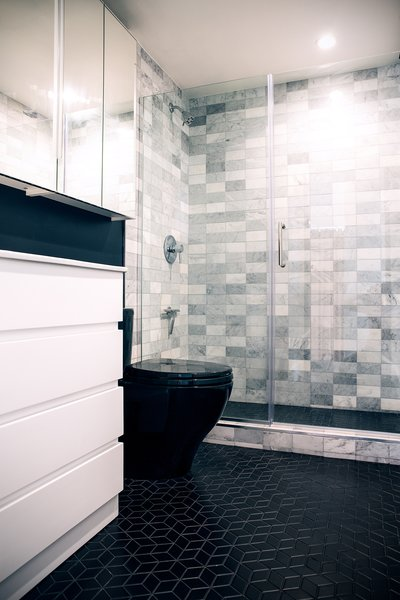 In the new bathroom, the couple chose black floor tile from Wayfair, in a shape similar to the kitchen tile for consistency. The marble shower tile was a Home Depot find, as was the Toto toilet.