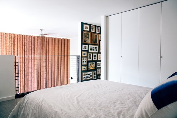 Now, the new railing enables sight lines from the bed and a dark-hued wall is filled with the couple's art and mementos from their travels.