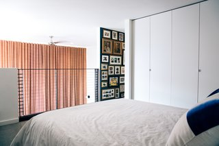 Now, the new railing enables sight lines from the bed, and a dark-hued wall is filled with the couple's art and mementos from their travels.