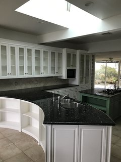 The '90s renovation had enlarged the kitchen and brought in an incompatible curved peninsula that chopped up the space.