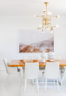 A burl dining table is surrounded by ivory chairs and topped with a distinct brass chandelier, all from AllModern. The large-scale landscape is by photographer Lou Mora.