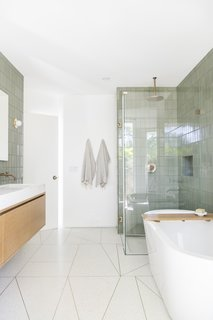Samuel designed the unique brass inlay pattern for the terrazzo floors, and the new glass-enclosed shower is an airy reprieve. All of the fixtures and faucets are from Wayfair.