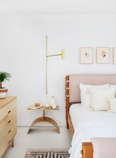 The terrazzo floors help to lighten and brighten the space. For furnishings, Samuel deftly mixes custom pieces with mass-market finds, combining a solid brass sconce from Dylan Grey and the Simple Dresser from Kalon Studios with an Anthropologie bed and CB2 side table.