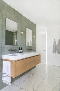 A custom vanity topped with marble floats against a wall clad in Fireclay Tile. The mirrors are by Wayfair and the sconces from Allied Maker.