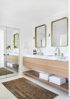The principal suite's bathroom features a custom white oak vanity topped with marble and decked with faucets from Rejuvenation. The CB2 mirrors are flanked by sconces from Foundry Lighting.