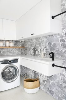 The laundry room off the kitchen also got a glam makeover. An Electolux washer and dryer set is tucked beneath a quartz counter for folding clothes. Black shower curtain rods provide space for hanging clothes to dry. They look sharp against statement wallpaper by Fornasetti. The cabinet hardware is by Sarah Sherman Samuel for Park Studio.