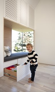 Perforated cabinet faces above the reading nook conceal an energy-efficient, mini-split heating and cooling system. Bleached and whitewashed maple lines the nook, while drawers below provide plenty of storage.