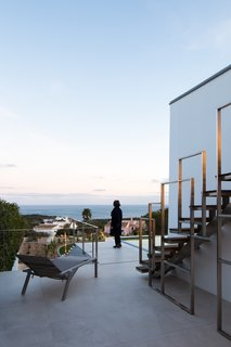 A bespoke metal staircase leads up to a rooftop observation deck.