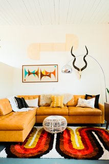 On the other side of the living room, Nagel combined a leather Joybird sectional sofa with an AllModern rug.