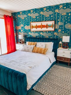 For a bedroom accent wall, Nagel chose Justina Blakeney's Cosmic Desert wallpaper in teal, also from Hygge and West, and paired it with a Joybird bed and bright red curtains.