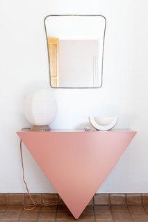 In a hallway, the Single Triangle Console powder-coated pink, from the Cuffhome collection, makes for a striking statement piece.