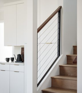 Stairs clad in the same wood as the floor, European oak, lead up to the second-floor addition, which is now home to a 500-square-foot principal suite.
