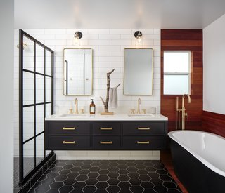 The palette of white, black, and brass continues in the principal bathroom.