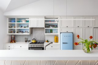 Kitchen appliances include a SMEG refrigerator, Bertazzoni Range Oven, and Bosch Dishwasher. The counters are honed white quartz, and the pendant over the island is the Cirrus Float by Edge Lighting.