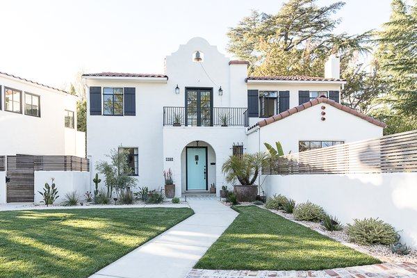 The couple introduced new landscaping and privacy walls, one of which screens off a new pool in the front yard. The exterior received a fresh coat of white stucco, architectural embellishment around the bell, and black paint on shutters and original metal windows.