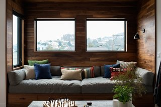 A walnut-wrapped nook in the living room of an apartment renovation in San Francisco by SF Design Build includes a built-in window seat that's complete with plush cushions and pillows. Multiple windows and a wall-mounted light ensure that the space receives plenty of light.