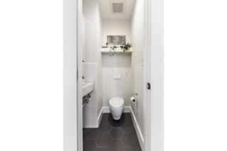 The new powder room includes a wall-hung Toto toilet and wall-hung Duravit sink, white subway wall tiles, and charcoal gray medium hex floor tiles to create a functional space that feels larger than it is.