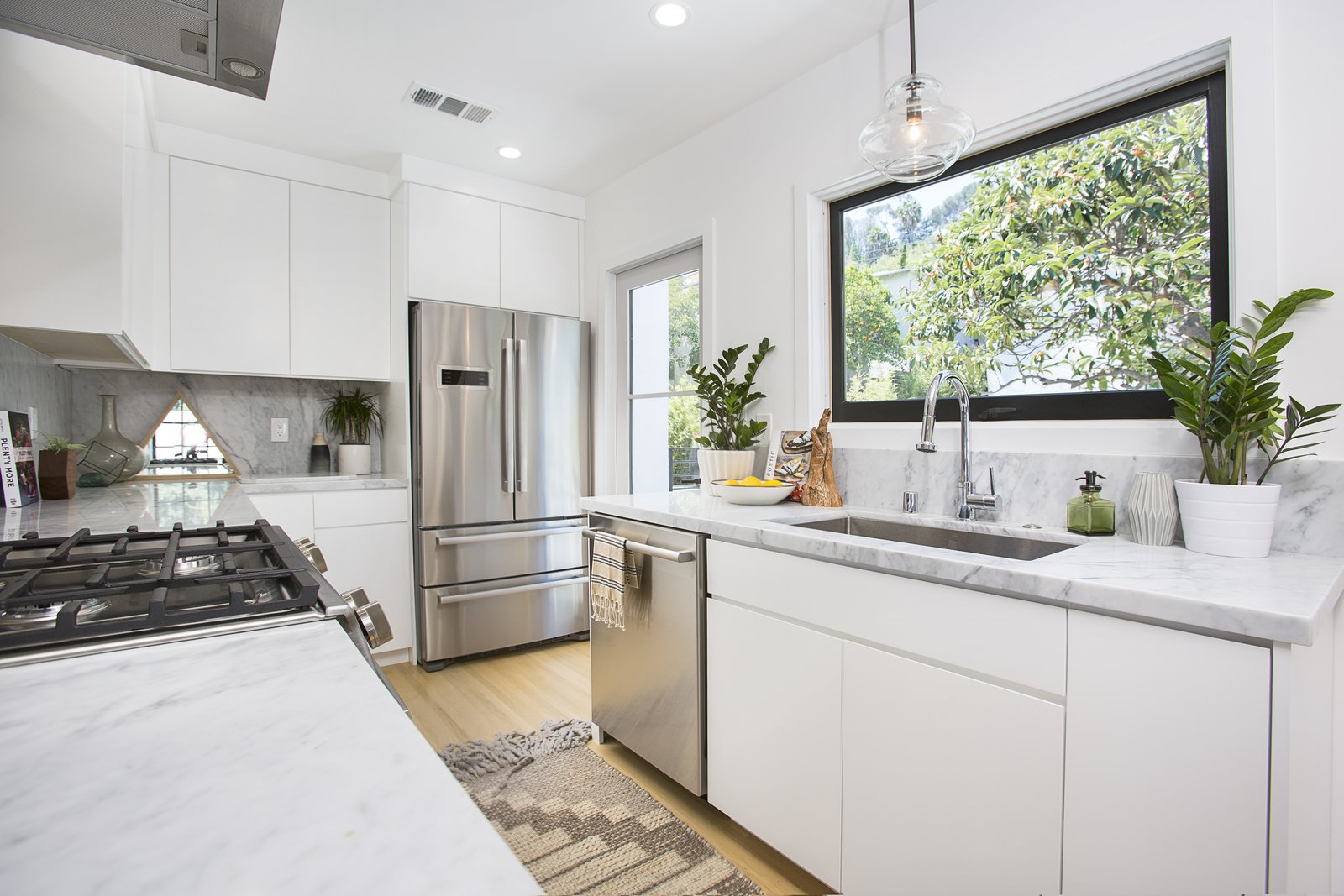Kitchen, White Cabinet, Marble Counter, Wood Cabinet, Ceiling Lighting, Recessed Lighting, Pendant Lighting, Light Hardwood Floor, Stone Slab Backsplashe, Refrigerator, Dishwasher, Range, Range Hood, and Undermount Sink  Silverlake on Riverside Terrace