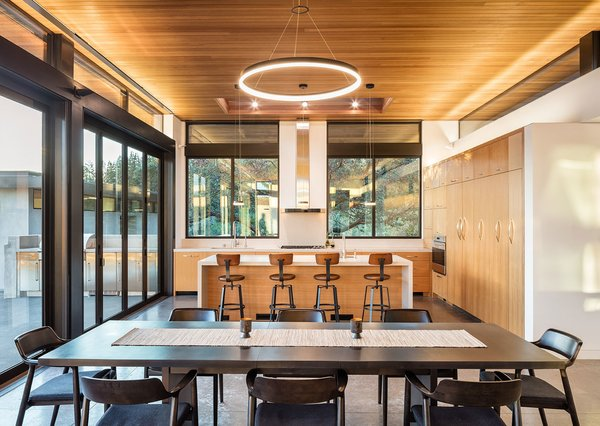 Table, Chair, Ceiling Lighting, Stools, Recessed Lighting, Kitchen, Concrete Floor, Wood Cabinet, Engineered Quartz Counter, Refrigerator, Wall Oven, Cooktops, Dishwasher, Undermount Sink, and Range Hood  Best Photos from Dry Creek Residence