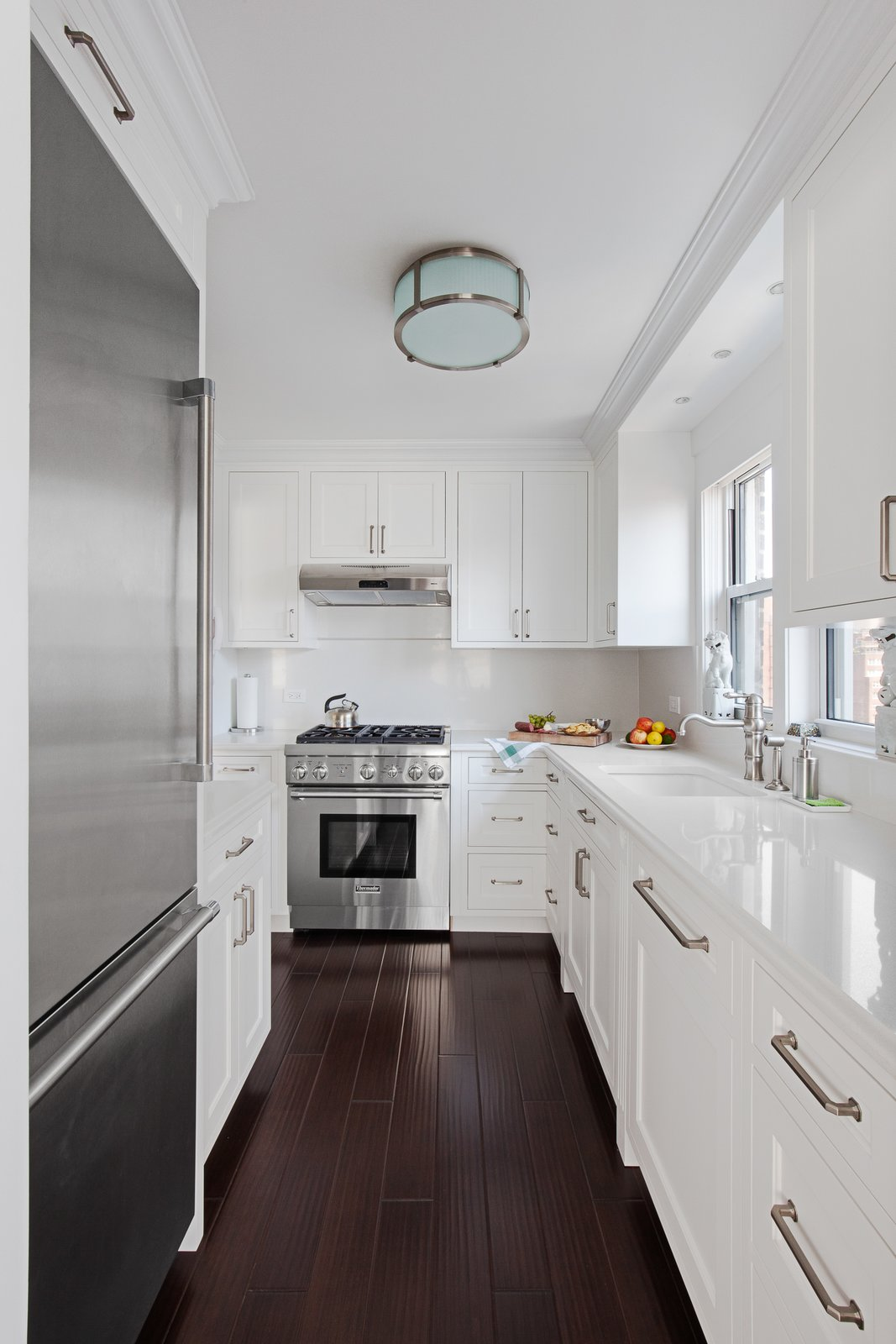 Kitchen, Dark Hardwood Floor, Refrigerator, Drop In Sink, Wall Oven, and White Cabinet  AN ART-FILLED APARTMENT RENOVATION 40 YEARS IN THE MAKING! by Pixy Interiors