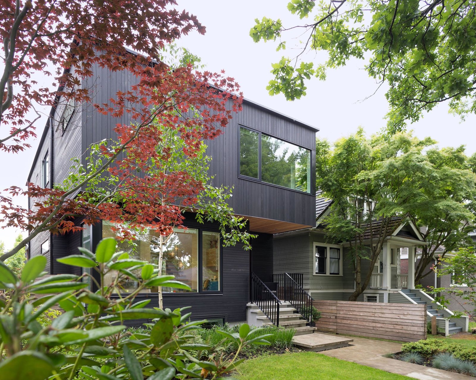 Outdoor, Front Yard, Trees, Grass, Shrubs, and Walkways The entryway of the Pink House is recessed to enhance the spatial notion of solid and void.  Photo 2 of 10 in Custom Millwork and Bright Interiors Star in an Elegant Vancouver Home