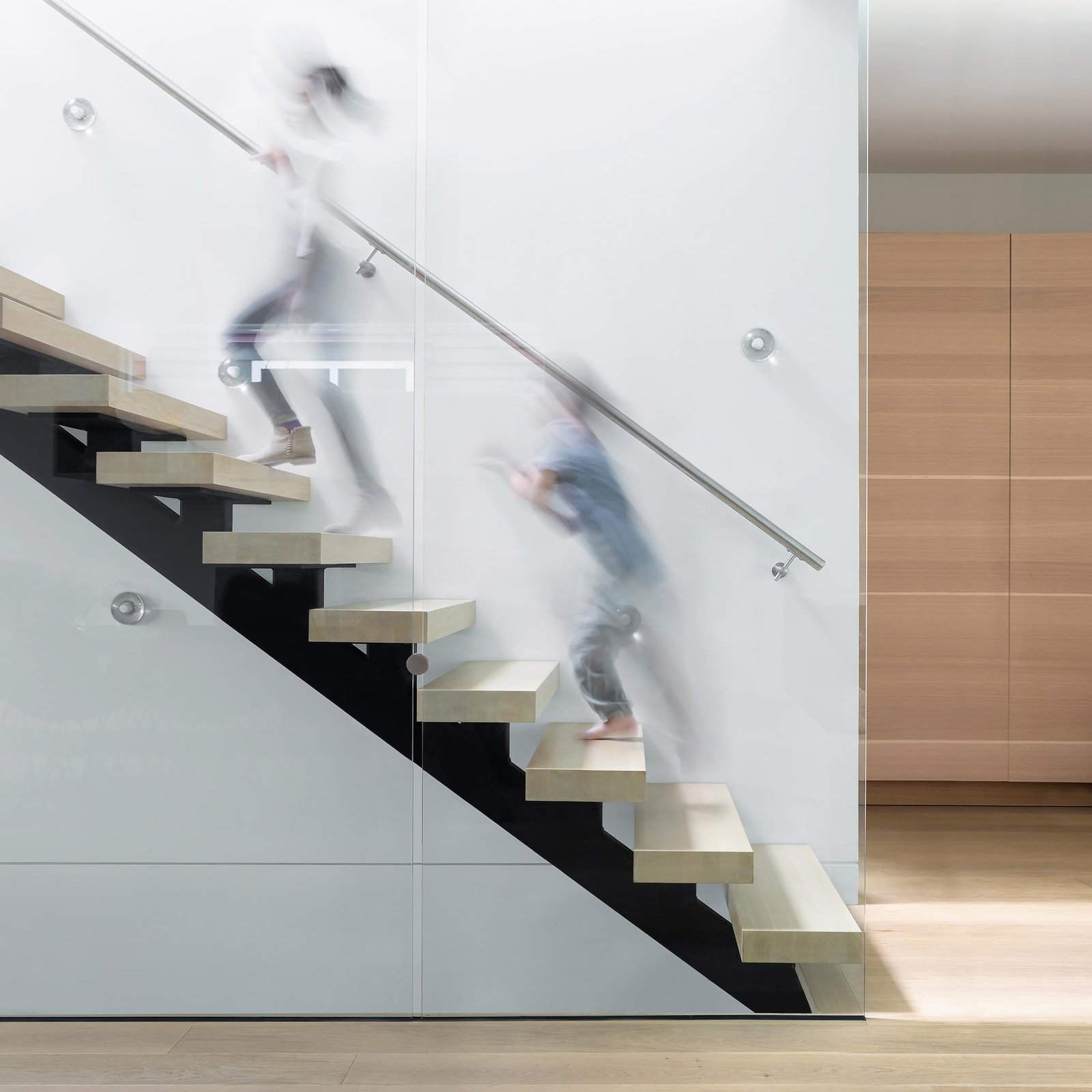 Staircase, Wood Tread, and Metal Railing The stair, an architectural piece in itself, composed of glass balustrades and open risers, allows light to fall further into the interior.  Photo 8 of 10 in Custom Millwork and Bright Interiors Star in an Elegant Vancouver Home