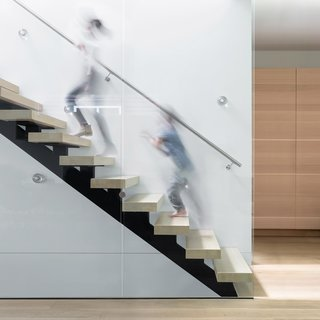 The stair, a sculptural piece composed of glass guards and open wood risers, allows light to fall further into the interior.
