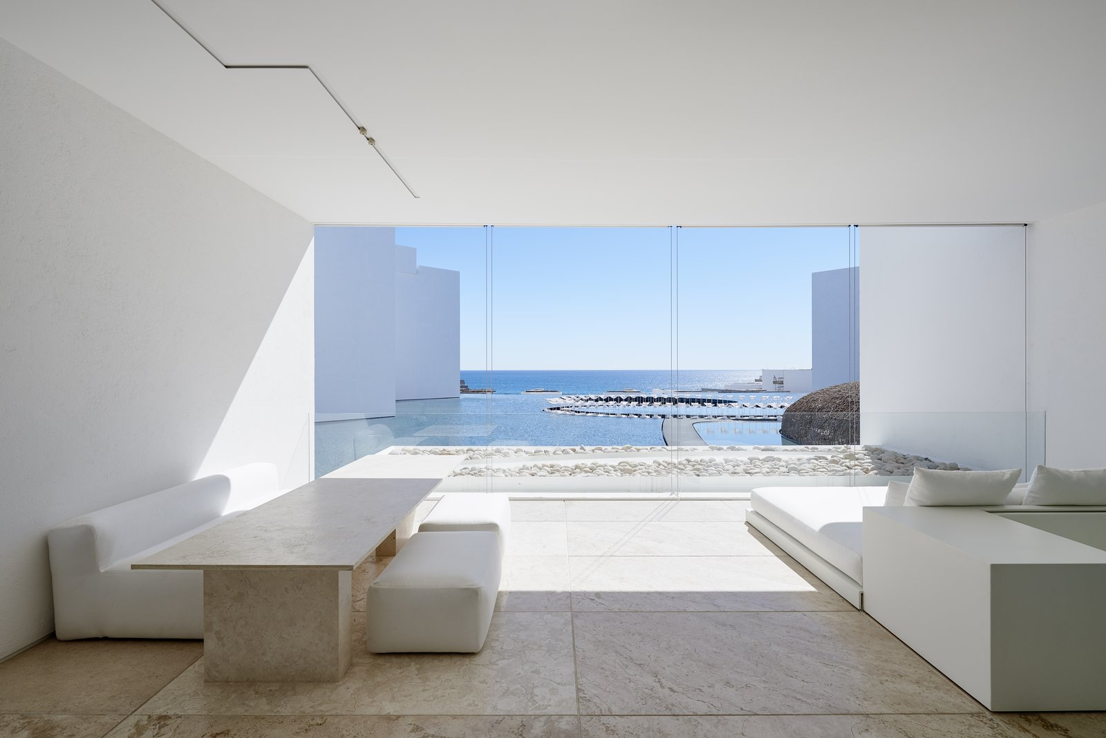 Living Room, Ceiling Lighting, Sofa, Travertine Floor, Bench, and Table Each room encases a private view of the ocean.  Photo 9 of 12 in An Exquisite Beach Resort on Baja California Sur Lies Where the Water Meets the Horizon