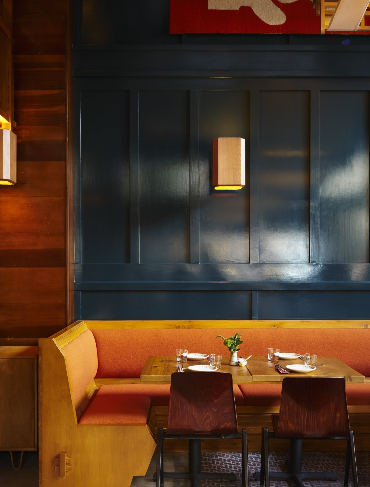 Custom millwork was designed with an arts and craft influence through details and shape, softened by rich fabrics. Tagged: Dining Room, Table, Bench, Chair, and Wall Lighting.  Photo 6 of 10 in A 1920s Office Building Is Revamped as a Craftsman-Inspired Hotel in Los Angeles